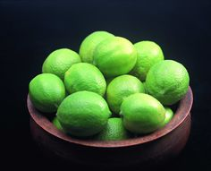 Heap of green lemons in a pot against a dark background