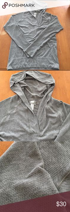 Lightweight Athleta hoodie Seamless, lightweight Athleta pullover hoodie. Heathered green/grey color. Sleeves are a different texture than the body with small perforations. There is a tiny bit of pilling under the arms (tried to capture it in the last photo), but it's hardly noticeable. Athleta Tops Sweatshirts & Hoodies