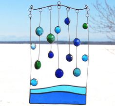 BERMUDA RAIN This handmade abstract glass and copper mobile is showing an aqua mixture of raindrops falling into a turquoise and blue sea. Fourteen glass nuggets including, 6 turquoise, 5 blue and 3 green; water glass of blue and turquoise; and copper wire were used to create it. It measures approximately 6x9 inches (15x22.5cm). Water, you are the one that brings us life. You are the source of nourishment that gives us strength. We rejoice in your existance. We drink you with joy... ~The…
