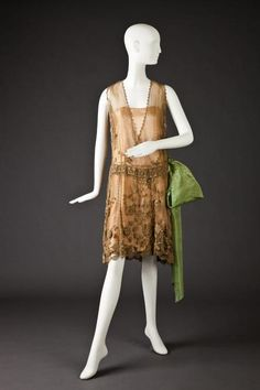 Dress 1928-1930    Ecru Lace Dress With Irish Crochet Floral Motif. Lined With Flesh Colored Chiffon and Satin, Large Green Moire Taffeta Bow At Dropped Waistline.  The Goldstein Museum of Design