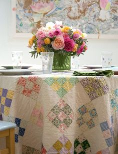A vintage 9-patch quilt used as a tablecloth, topped with a pretty vase of colorful roses