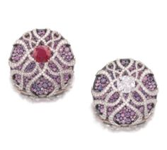 PAIR OF SUPERB SAPPHIRE, RUBY AND DIAMOND EARRINGS, JAR Each of circular form, pavé-set with circular-cut sapphires of various hues ranging from light pink to purplish blue, surmounted with a stylised cage set with a cushion-shaped stone, one a diamond weighing 3.06 carats, the other a ruby weighing 4.89 carats, and lines of single-cut diamonds, signed JAR, French import marks, post and hinged back fittings, case by JAR.  Credit - Sotheby's