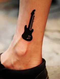 Minimalist guitar tattoo on the ankle. The silhouette of the guitar gives a good contrast on the ankle as it can be noticed even from afar.