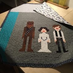 Maeby has been busy! I left for yoga class and came back to find that she not only finished the quilting, but made binding too! All that's left is to hand (paw?) finish the binding.  (P.S. More #rhodaruthfabric and #ehpacificfabric in this one. Novelty Star Wars print on the back. Blocks adapted from @weelittlestitches cross stitch pattern.)