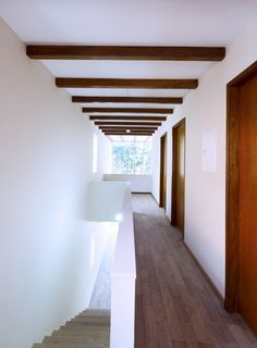 Corridor in white plaster and wood. The Floradas House by Obra Arquitectors. Photo by Rafael P. Schimidt.