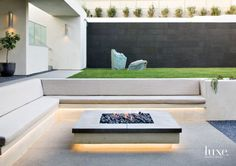 A clean, modern fire pit is flanked by a built-in bench topped with custom cushi. A clean, modern fire pit is flanked by a built-in bench topped with custom cushions that blend into the calm, neutral co. Modern Landscape Design, Modern Landscaping, Backyard Landscaping, Landscaping Ideas, Backyard Ideas, Modern Backyard Design, Firepit Ideas, Fence Ideas, Garden Ideas