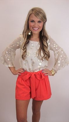 Obsessed with the gold detailing on the creme top, paired with coral high waisted shorts.