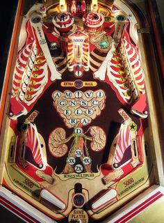 """The playing surface of Howie Tsui's pinball machine Musketball! Health-care on the battlefield of the War of 1812 was a harsh business, but now it's fun!"""""""