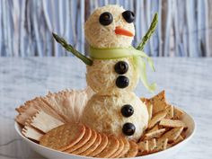 Snowman Cheese Ball : A classic cheese ball is transformed into a festive holiday hors d'oeuvre with a few simple additions, like a carrot nose and black-olive eyes. Serve with crackers for a silly (and, of course, delicious) party snack.