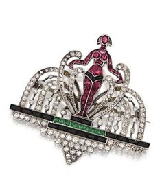 ART DECO DIAMOND, ONYX AND SIMULATED COLORED STONE BROOCH, CIRCA 1925. Designed as a woman standing in the center of a fountain, her body accented with calibré-cut synthetic rubies, standing on a platform of calibré-cut onyx and synthetic emeralds, completed by numerous single-cut diamonds, mounted in platinum.