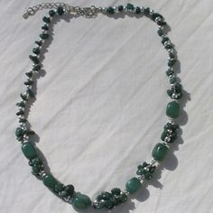 NOT AVAILABLE This necklace is brand new. It consists of green colored stones (don't know what kind) and silver colored beads. Very pretty and perfect for your green item on St. Patrick's Day! Jewelry Necklaces