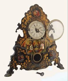 Charming antique mantle clock with ebonized, painted and applied shell decor to metal front. Decoration depicts a castle in a landscape surrounded by flowers and rests on two, goat hoof shaped feet. c 19th century. $650 on GoAntiques.com