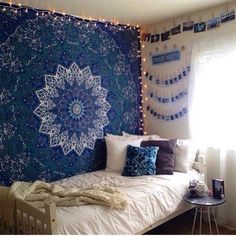 pictures above bed with tapestry. bed in corner of room near window with small nightstand.