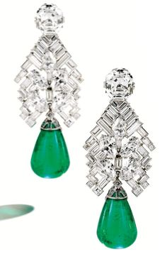 Art Deco emerald and diamond earrings by Cartier, circa 1934. These earrings are topped by one emerald-cut diamond weighing 4.78 carats and one cut-cornered rectangular step-cut diamond weighing 4.77 carats. The diamond surmounts suspend an articulated chevron motif set with numerous baguette, square-cut and marquise-shaped diamonds weighing a total of approximately 11.25 carats.