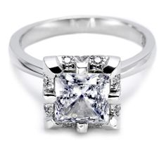 Enhance a princess-cut center stone with a bright crown of large round diamonds and mirror-finish platinum prongs. A high-polished band gives it a sophisticated finish.