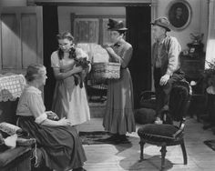 Examples of Foreshadowing in Narratives: In this scene from early in the film <i>The Wizard of Oz</i> (1939), Almira Gulch (second from the right) arrives to take away Dorothy's dog Toto. Margaret Hamilton, the actress who played Miss Gulch, appears later in the movie as the Wicked Witch of the West