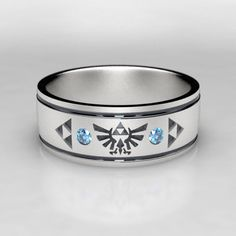 A tribute to Legend of Zelda in a unique mens wedding band! This ring comes with 2 round teal blue diamonds for nice accent stones. Also available with lab created rubies, emeralds, or sapphires upon request. This 7mm wide wedding band is made from recycled silver and is handmade with a comfort fit to your size. The ring is carved from wax, then cast in the metal. From there it is finished by hand to achieve a great wearable look. Ring Specs: ● 7mm width ● 1.5mm Thickness- good weight…