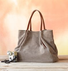 The simple beauty of suede shines in our unique, large, gathered handbag with leather handles and rivets.