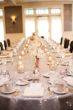 Pretty table setting with sequin tablecloth, ivory flowers and mercury candle holders.