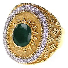 Materials 18k Gold, Diamonds and an Emerald. Specifics The face is approx 7/8 inch long by 3/4 inch wide. The ring will be made to your size by the designer for a perfect fit.