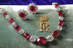 This ruby and diamond jewelry belonged to Mary, Duchess of Roxburghe, and was probably purchased from Garrards (a British jewelry since 1735) by the 5th Earl of Roseberry. The jewelry rests on its original turquoise velvet case, embellished with an R monogram that sits under a coronet (R&S Garrard & Co, Goldsmith and Jewellers to The Crown).