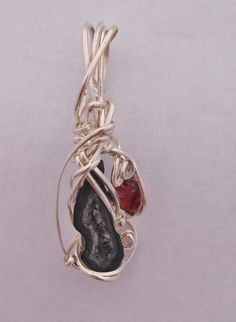 A sterling silver wire wrapped pendant featuring a Tabasco geode (I absolutely love these little guys) and a garnet accent.