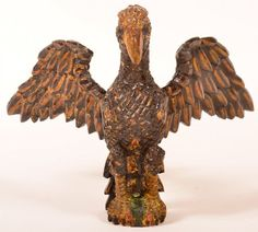 Wilhelm Schimmel Carved Spread Wing Eagle. : Lot 613 Wilhelm Schimmel (Cumberland Valley, PA, 1817-1890) Carved and Painted Spread Wing Eagle. Brown body with yellow highlights and green base .Ex. collection of El Roy P. and Helene Master. 10'' h., 13 1/4'' w. Condition: Left wing replaced, repair at neck and some points on right wing. Harry Hartman Sold $4300