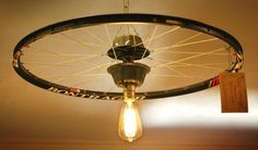 """I didn't reinvent the """"wheel"""" on this project.  Others have had their own twists to using bicycle parts for different repurposing.  But this is my take on it.  I got a hold of some great bicycle parts lately including a couple of racing rims.  I figure the white spokes and racing graphics on the rim would have great appeal.  A reproduction antique bulb brings the light into the equation. Repurposed Bicycle Rim Pendant Light Fixture - JUNKMARKET Style"""