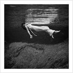 Photograph shows underwater view of a model, wearing a long gown, floating in water. Weeki Wachee spring, Florida. (1947)