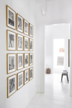 Good way to make a statement or focal point inexpensively using small framed art grouped together to make a large impact... Heller Flur - www.leuchtend-grau.de