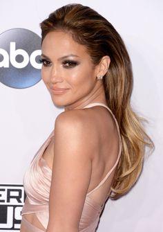 Makeup: Metallic black statement smokey eyes makeup,peachy tan cheeks, with glossy nude lips. Hair: Elegant structure volume sleek loose hairstyle. Jennifer Lopez at American Music Awards 2014 AMAs.