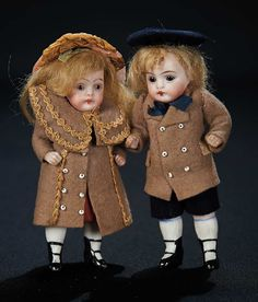 "Delightful Pair of German All-Bisque Miniature Dolls in Original Costumes 4"" (10 cm.) Each is one-piece bisque head and torso,tiny brown glass inset eyes,painted features,closed mouth,blonde mohair wig,jointed bisque arms and legs,painted white stockings and black two-strap heeled shoes. Condition: generally excellent. Comments: Germany,circa 1900. Value Points: the little boy and girl wear their matching factory-original costumes."