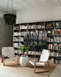 The library features a wall papered in a print by Neisha Crosland and a photograph by Ellen Kooi is displayed in front of modular metal book...