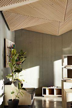 murs en béton et lambris plafond futuriste en lamelles de bois