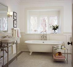 Baño de estilo vintage con azulejo blanco y bañera retro. El espejo es grande y la luz esta bien repartida por la estancia.
