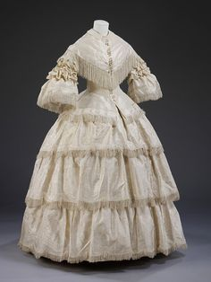 "Wedding Dress, England, Great Britain: 1857 (made), Figured silk trimmed with silk fringe, buckram stiffening.    ""Wedding dress of ivory figured silk with a pattern woven 'en disposition' of formal flowers with an undulating band above and a scalloped band below.    The dress consists of the evening bodice attached to the skirt. The bodice has a low, wide, pointed neckline, short straight sleeves covered with gathered bands of matching tulle, and a point front and back. The waist is trimmed..."