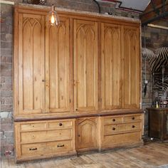This large Victorian Gothic Revival pine housekeeper's cabinet was salvaged from a large period property in Haworth, Yorkshire. Featuring five tall doors in the upper cupboard with shelving inside. A breakfront base with graduated drawers flanks a central cupboard. The cabinet is well worn and a number of the knobs are missing, in keeping with the cabinet's age. A wonderful piece offering a large amount of storage, well-suited for retail space.Please note, as the cabinet was originally…