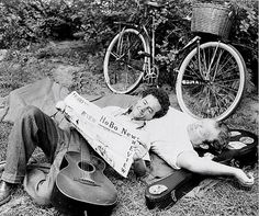 Woody Guthrie uses Burl Ives as a pillow while he reads Hobo News.