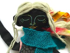 Tessa, a handmade cloth doll from black fabric. Face made of embroidery, hand knitted scarf.