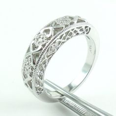 For sale is a 14k white gold ring band with thick fancy filigree open work and small diamond accents in excellent condition. Ring size is 6.75. It is