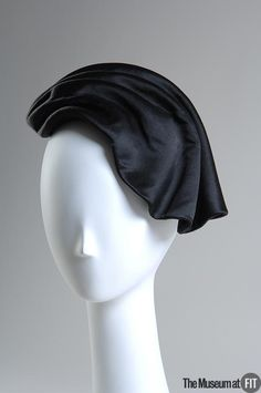 Black silk satin hat | Cristóbal Balenciaga (Spanish, 1895-1972) | France, circa 1955 | Balenciaga's millinery ranged from minimalist, sculptural designs to dramatic tributes to his Spanish heritage. Hats played an important part in the total look that he created. As with his clothes, Balenciaga's hats were not intended to be conventionally pretty, but rather were intended to provide the finishing touches for his bold architectural silhouettes.