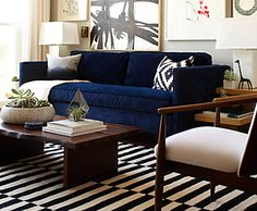 Layer a black and white striped rug atop the floor to embolden a blue couch. Find ways to incorporate other touches of black, whether in the artwork or the patterned pillows.