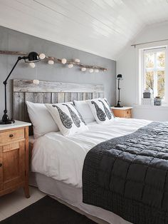 Bedroom in grey and white with wooden headboard via Design Traveller