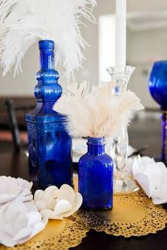 Blue bottles, white feathers, and metallic gold doilies - such a stunning color palette