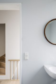 Beside the bedroom, off the hall, is a small bathroom, painted in a proprietary shade of blue from Boss Paints. The sink is by Duravit and the mirror is the client's own. #remodelista #bathroom #minimalist