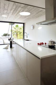 Cuisine blanche et taupe au look design dans une villa réaménagée par l'architecte DPLG Frédérique Pyra.