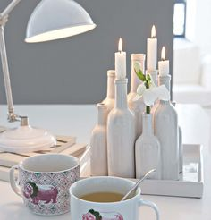 bottles painted white and grouped with candles and flowers