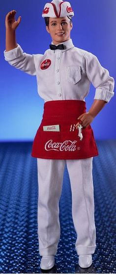 2000. Pop Culture. COCA-COLA Barbie Series. COCA-COLA Ken Doll.  COCA-COLA script trademark adorns his clothes and a very special miniature bottle opener attaches to his apron. He even has a writing pad, pencil and straws for two.