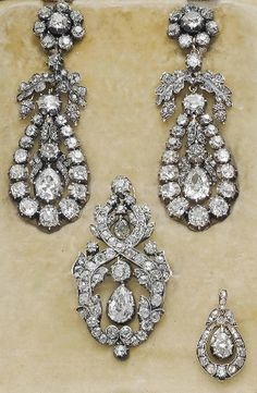 A GROUP OF ANTIQUE DIAMOND JEWELLERY  Comprising a pair of Georgian ear pendants, each designed as an old-cut diamond cluster top suspending a detachable drop-shaped pendant centering upon a pear-shaped diamond with foliate detail, early 19th Century, 7.5 cm, together with an associated pendant/brooch and a smaller pendant, mid-19th Century, brooch 5.0 cm, pendant 2.5 cm, all mounted in silver and gold, in beige suede Hancocks case.