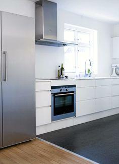Beboeren valgte en hvit innredning og benkeplate for å lysne rommet, mens det mørke gulvet skaper dybde. Kjøkkeninnredningen er fra Invita, og hvitevarene er fra Siemens.